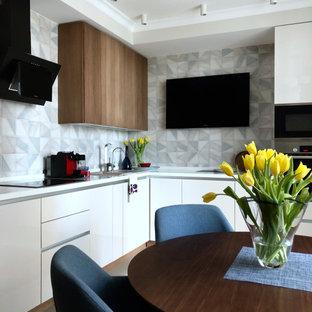 На фото: угловая кухня среднего размера в современном стиле с обеденным столом, плоскими фасадами, белыми фасадами, серым фартуком, техникой из нержавеющей стали, серым полом и белой столешницей с
