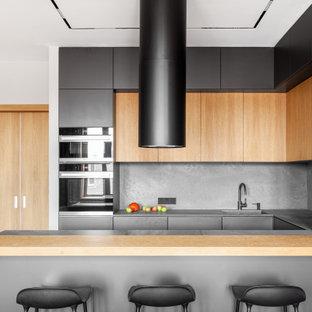 На фото: п-образная кухня в современном стиле с врезной раковиной, плоскими фасадами, серыми фасадами, серым фартуком, черной техникой, полуостровом и черной столешницей