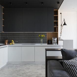На фото: угловая кухня-гостиная в скандинавском стиле с плоскими фасадами, черными фасадами, черным фартуком, серым полом и белой столешницей без острова