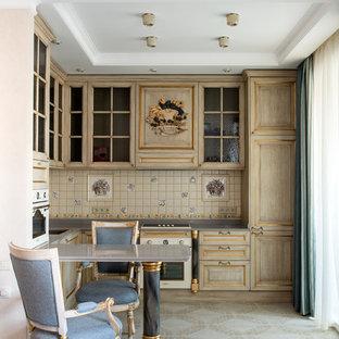 На фото: угловая кухня в классическом стиле с светлыми деревянными фасадами, фартуком из керамической плитки, белой техникой, серой столешницей, фасадами с выступающей филенкой, разноцветным фартуком, полуостровом и разноцветным полом