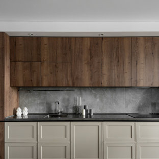 This is an example of a mid-sized contemporary single-wall kitchen in Other with an integrated sink, shaker cabinets, beige cabinets, grey splashback, porcelain splashback, panelled appliances, porcelain floors, no island, brown floor and black benchtop.