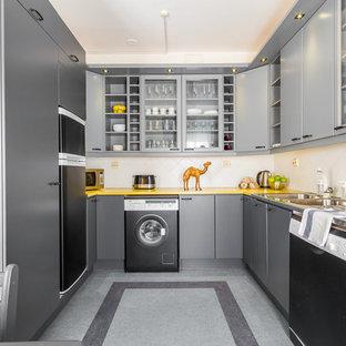 Идея дизайна: п-образная кухня в скандинавском стиле с накладной раковиной, плоскими фасадами, серыми фасадами, белым фартуком, черной техникой, серым полом и желтой столешницей