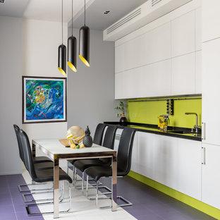 Новые идеи обустройства дома: линейная кухня среднего размера в стиле фьюжн с черной столешницей, обеденным столом, одинарной раковиной, плоскими фасадами, белыми фасадами, зеленым фартуком и фиолетовым полом без острова