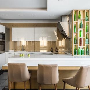 Создайте стильный интерьер: п-образная кухня в современном стиле с плоскими фасадами, белыми фасадами, бежевым фартуком, техникой из нержавеющей стали, полуостровом, черным полом и фартуком из стекла - последний тренд