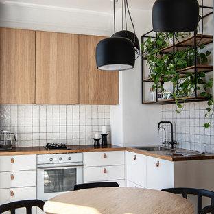 Идея дизайна: угловая кухня-гостиная в скандинавском стиле с плоскими фасадами, белыми фасадами, белым фартуком, белой техникой, светлым паркетным полом, бежевым полом и коричневой столешницей без острова