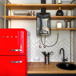 Неиссякаемый источник вдохновения для домашнего уюта: маленькая отдельная, параллельная кухня в скандинавском стиле с плоскими фасадами, черными фасадами, столешницей из дерева, серым фартуком, коричневой столешницей, накладной раковиной и фартуком из плитки кабанчик
