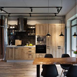 モスクワの中サイズのインダストリアルスタイルのおしゃれなキッチン (ラミネートの床、茶色い床、ドロップインシンク、人工大理石カウンター、黒いキッチンパネル、セラミックタイルのキッチンパネル、シルバーの調理設備の、アイランドなし、シェーカースタイル扉のキャビネット、淡色木目調キャビネット) の写真