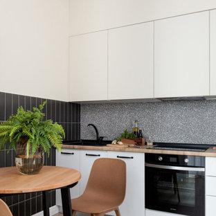 На фото: линейные кухни в современном стиле с плоскими фасадами, белыми фасадами, серым фартуком, черной техникой, светлым паркетным полом, бежевым полом и коричневой столешницей без острова