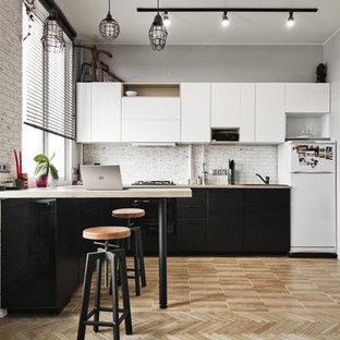 Стильный дизайн: кухня-гостиная среднего размера в стиле лофт с плоскими фасадами, черной техникой и коричневым полом без острова - последний тренд