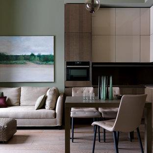 На фото: со средним бюджетом угловые кухни-гостиные среднего размера в современном стиле с плоскими фасадами, паркетным полом среднего тона, коричневым полом, черной техникой, коричневой столешницей и бежевыми фасадами без острова