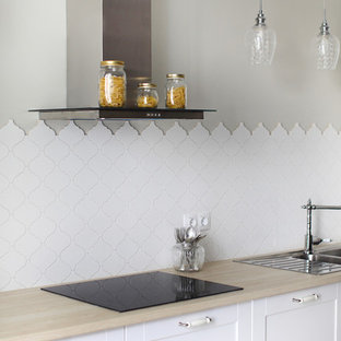 Inspiration for a mid-sized transitional single-wall kitchen in Saint Petersburg with white cabinets, wood benchtops, white splashback, ceramic splashback, a drop-in sink, beige benchtop and recessed-panel cabinets.