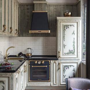 Идея дизайна: маленькая п-образная кухня в викторианском стиле с фасадами с выступающей филенкой, серыми фасадами, столешницей из кварцевого агломерата, фартуком из керамической плитки, черной столешницей, раковиной в стиле кантри, белым фартуком, техникой под мебельный фасад, темным паркетным полом и коричневым полом