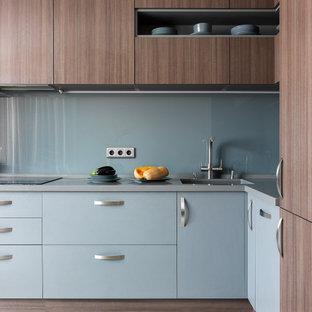 На фото: угловая кухня в современном стиле с врезной раковиной, плоскими фасадами, синими фасадами, столешницей из нержавеющей стали, фартуком из стекла, техникой из нержавеющей стали, серым полом и серой столешницей без острова