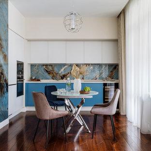 Свежая идея для дизайна: угловая кухня среднего размера в современном стиле с обеденным столом, врезной раковиной, плоскими фасадами, белыми фасадами, синим фартуком, техникой под мебельный фасад, паркетным полом среднего тона, коричневым полом и белой столешницей без острова - отличное фото интерьера