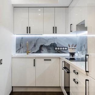 Стильный дизайн: угловая кухня-гостиная в современном стиле с накладной раковиной, плоскими фасадами, белыми фасадами, серым фартуком, фартуком из каменной плиты, черной техникой и темным паркетным полом без острова - последний тренд