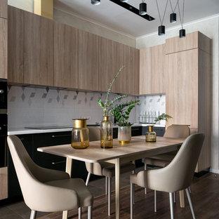 Пример оригинального дизайна: угловая кухня среднего размера в современном стиле с обеденным столом, плоскими фасадами, светлыми деревянными фасадами, столешницей из акрилового камня, фартуком из керамической плитки, полом из ламината, коричневым полом, белой столешницей и разноцветным фартуком