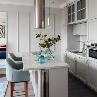 Новые идеи обустройства дома: маленькая параллельная кухня в стиле современная классика с врезной раковиной, фасадами с утопленной филенкой, серыми фасадами, столешницей из кварцевого композита, белым фартуком, фартуком из мрамора, техникой из нержавеющей стали, паркетным полом среднего тона, островом, серым полом и белой столешницей