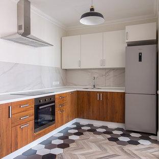 Пример оригинального дизайна интерьера: угловая кухня в современном стиле с накладной раковиной, плоскими фасадами, фасадами цвета дерева среднего тона, серым фартуком, техникой из нержавеющей стали, разноцветным полом и белой столешницей без острова