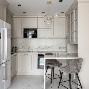 На фото: п-образные кухни среднего размера в стиле современная классика с фасадами с утопленной филенкой, бежевыми фасадами, серым фартуком, полом из керамогранита, полуостровом, серым полом и белой столешницей
