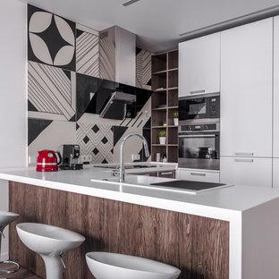 Стильный дизайн: п-образная кухня среднего размера в современном стиле с обеденным столом, плоскими фасадами, белыми фасадами, столешницей из акрилового камня, фартуком из керамогранитной плитки, накладной раковиной, техникой из нержавеющей стали, полуостровом, белой столешницей и разноцветным фартуком - последний тренд