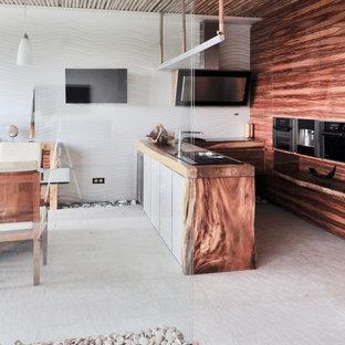 Свежая идея для дизайна: п-образная кухня-гостиная среднего размера в современном стиле с плоскими фасадами, фасадами цвета дерева среднего тона, белым фартуком, техникой из нержавеющей стали, полуостровом, белым полом, врезной раковиной, столешницей из дерева, полом из керамогранита, фартуком из керамической плитки и коричневой столешницей - отличное фото интерьера