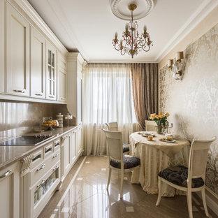 Стильный дизайн: большая прямая кухня в классическом стиле с обеденным столом, фасадами с утопленной филенкой, бежевыми фасадами, бежевым фартуком, фартуком из каменной плиты, бежевым полом и бежевой столешницей - последний тренд