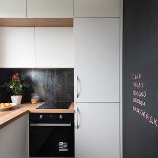 На фото: маленькая отдельная, угловая кухня в современном стиле с плоскими фасадами, белыми фасадами, черным фартуком, черной техникой, коричневым полом и коричневой столешницей без острова с