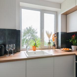 На фото: маленькая отдельная, угловая кухня в современном стиле с накладной раковиной, плоскими фасадами, белыми фасадами, черным фартуком, коричневым полом и коричневой столешницей без острова