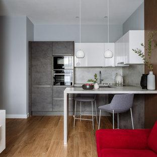 На фото: п-образная кухня-гостиная среднего размера в современном стиле с накладной раковиной, плоскими фасадами, серыми фасадами, серым фартуком, фартуком из керамогранитной плитки, техникой под мебельный фасад, паркетным полом среднего тона, полуостровом, коричневым полом и серой столешницей