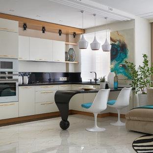 На фото: угловые кухни-гостиные в стиле фьюжн с плоскими фасадами, белыми фасадами, черным фартуком, белым полом, черной столешницей, техникой из нержавеющей стали и полуостровом