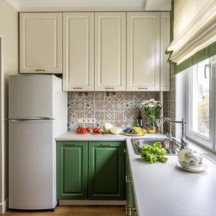 Пример оригинального дизайна: маленькая отдельная, угловая кухня в стиле современная классика с фасадами с выступающей филенкой, зелеными фасадами, столешницей из ламината, фартуком из керамической плитки, накладной раковиной и разноцветным фартуком без острова
