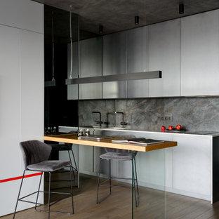 Идея дизайна: угловая кухня в современном стиле с обеденным столом, плоскими фасадами, белыми фасадами, серым фартуком, техникой под мебельный фасад, паркетным полом среднего тона, коричневым полом и белой столешницей без острова