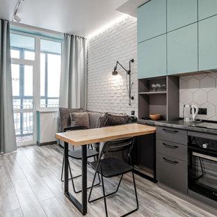 Неиссякаемый источник вдохновения для домашнего уюта: линейная кухня-гостиная в скандинавском стиле с плоскими фасадами, бирюзовыми фасадами, белым фартуком, черной техникой, серым полом и черной столешницей без острова