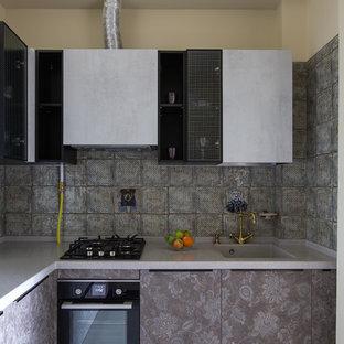 На фото: угловая кухня в современном стиле с монолитной раковиной, плоскими фасадами, серыми фасадами, серым фартуком, черной техникой, серым полом и серой столешницей