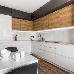 他の地域の中サイズのコンテンポラリースタイルのおしゃれなキッチン (シングルシンク、フラットパネル扉のキャビネット、白いキャビネット、人工大理石カウンター、白いキッチンパネル、ガラス板のキッチンパネル、黒い調理設備、クッションフロア、アイランドなし、ベージュの床、ベージュのキッチンカウンター) の写真