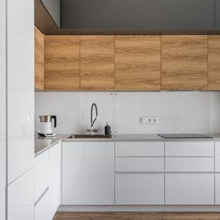 他の地域の中くらいのコンテンポラリースタイルのおしゃれなキッチン (シングルシンク、フラットパネル扉のキャビネット、白いキャビネット、人工大理石カウンター、白いキッチンパネル、ガラス板のキッチンパネル、黒い調理設備、クッションフロア、アイランドなし、ベージュの床、ベージュのキッチンカウンター) の写真