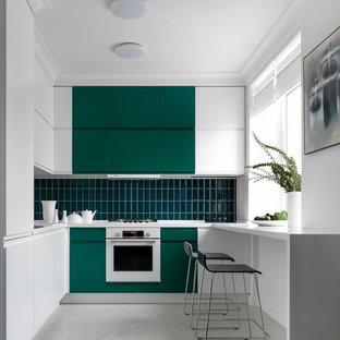 Свежая идея для дизайна: угловая кухня среднего размера в современном стиле с плоскими фасадами, зелеными фасадами, зеленым фартуком, белой техникой, серым полом и белой столешницей без острова - отличное фото интерьера