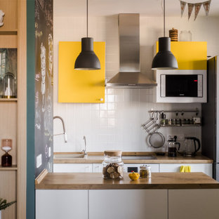 Источник вдохновения для домашнего уюта: кухня в современном стиле с накладной раковиной, плоскими фасадами, желтыми фасадами, белым фартуком, белой техникой, полуостровом и коричневой столешницей