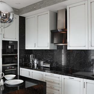 Новые идеи обустройства дома: угловая кухня-гостиная в современном стиле с накладной раковиной, фасадами с утопленной филенкой, белыми фасадами, черным фартуком, черной техникой и островом