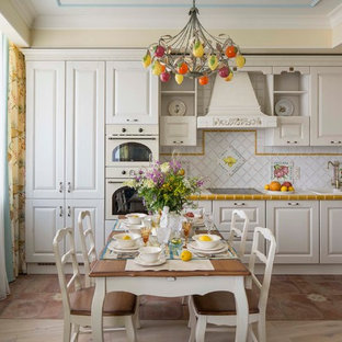 This is an example of a traditional l-shaped eat-in kitchen in Moscow with raised-panel cabinets, white cabinets, white splashback, white appliances and no island.