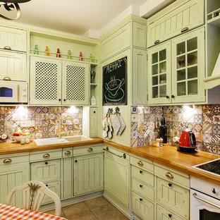 На фото: отдельные, угловые кухни в стиле кантри с накладной раковиной, зелеными фасадами, разноцветным фартуком, белой техникой и коричневым полом без острова