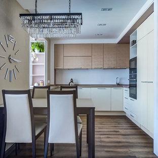 Неиссякаемый источник вдохновения для домашнего уюта: кухня-гостиная в современном стиле с белыми фасадами, белым фартуком и коричневым полом