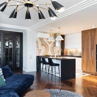 Свежая идея для дизайна: п-образная кухня-гостиная в современном стиле с плоскими фасадами, белыми фасадами, черной техникой, полуостровом и черной столешницей - отличное фото интерьера