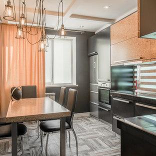 На фото: отдельные, угловые кухни в стиле лофт с плоскими фасадами, черными фасадами, техникой из нержавеющей стали и серым полом