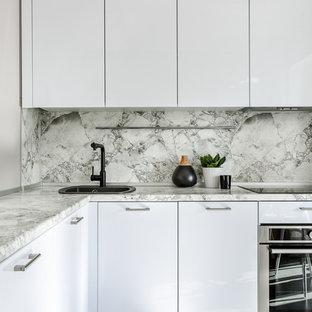 На фото: отдельная, угловая кухня в современном стиле с накладной раковиной, плоскими фасадами, белыми фасадами, серым фартуком, техникой из нержавеющей стали и серым полом