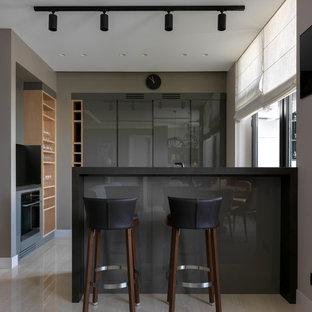 На фото: кухня-гостиная среднего размера в современном стиле с плоскими фасадами, серыми фасадами, полуостровом и бежевым полом