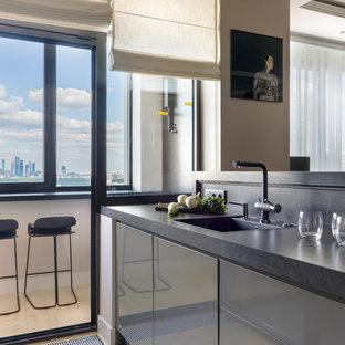 Неиссякаемый источник вдохновения для домашнего уюта: линейная кухня-гостиная среднего размера в современном стиле с плоскими фасадами, серыми фасадами, серым фартуком, фартуком из керамогранитной плитки, мраморным полом, полуостровом, бежевым полом, черной столешницей, накладной раковиной и гранитной столешницей