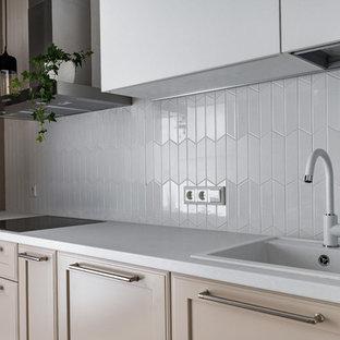 На фото: отдельная, угловая кухня в скандинавском стиле с накладной раковиной, фасадами с утопленной филенкой, бежевыми фасадами, белым фартуком и белой столешницей с