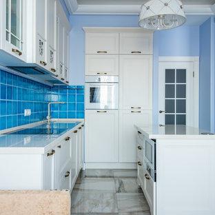 Неиссякаемый источник вдохновения для домашнего уюта: линейная кухня в стиле современная классика с обеденным столом, фасадами с утопленной филенкой, белыми фасадами, синим фартуком, белой техникой, островом и бежевым полом