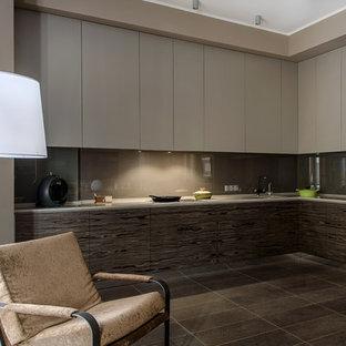 Свежая идея для дизайна: угловая кухня-гостиная в современном стиле с врезной раковиной, плоскими фасадами, коричневым фартуком, техникой из нержавеющей стали и коричневым полом без острова - отличное фото интерьера